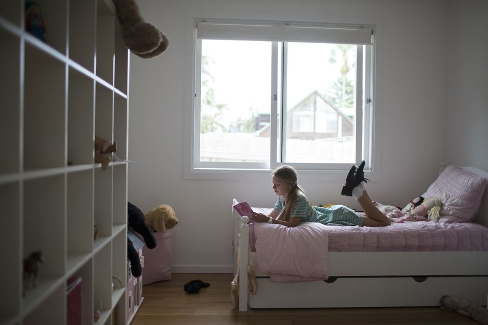 School girl reading in bedroom at home