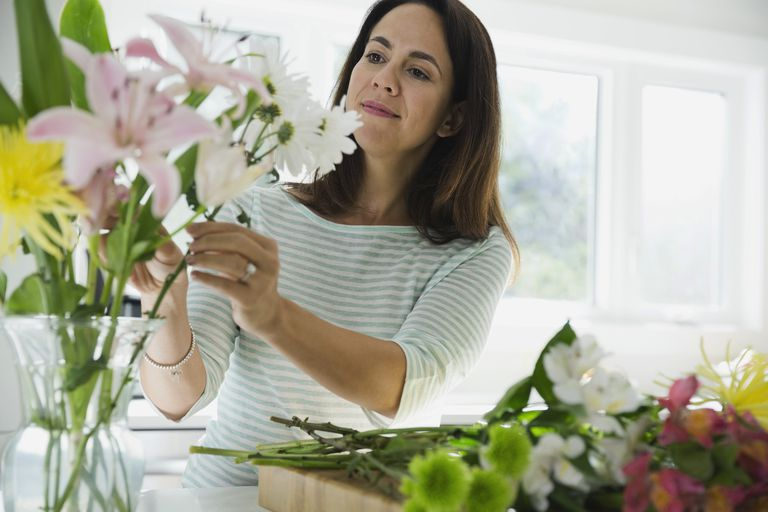 Woman arranging flowers in vase at home