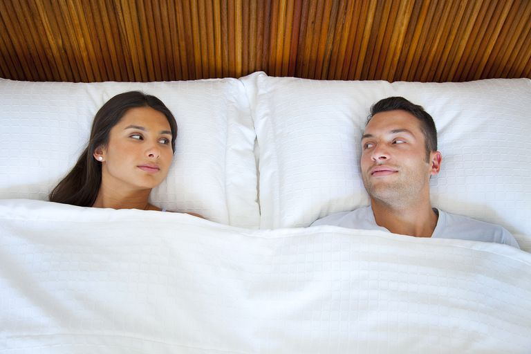 couple in bed looking at each other
