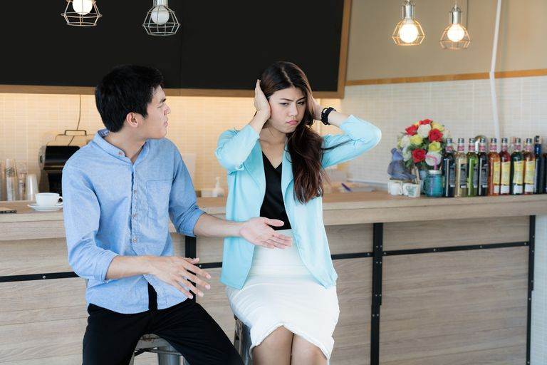 Frustrated young Asian couple having argument and quarrelling with each other and woman closing her ears. Couple having argument - conflict, bad relationships.