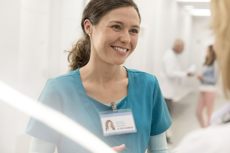 Smiling nurse talking to doctor in hospital corridor