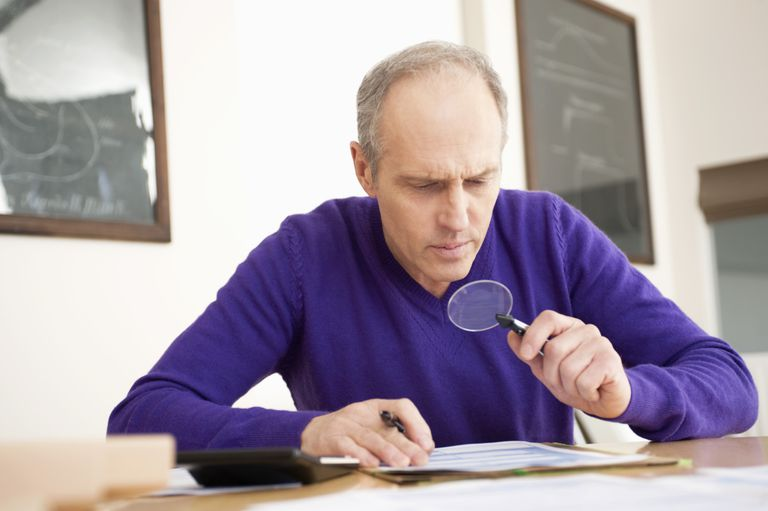 Man looking through magnifying glass as the estate tax rules.