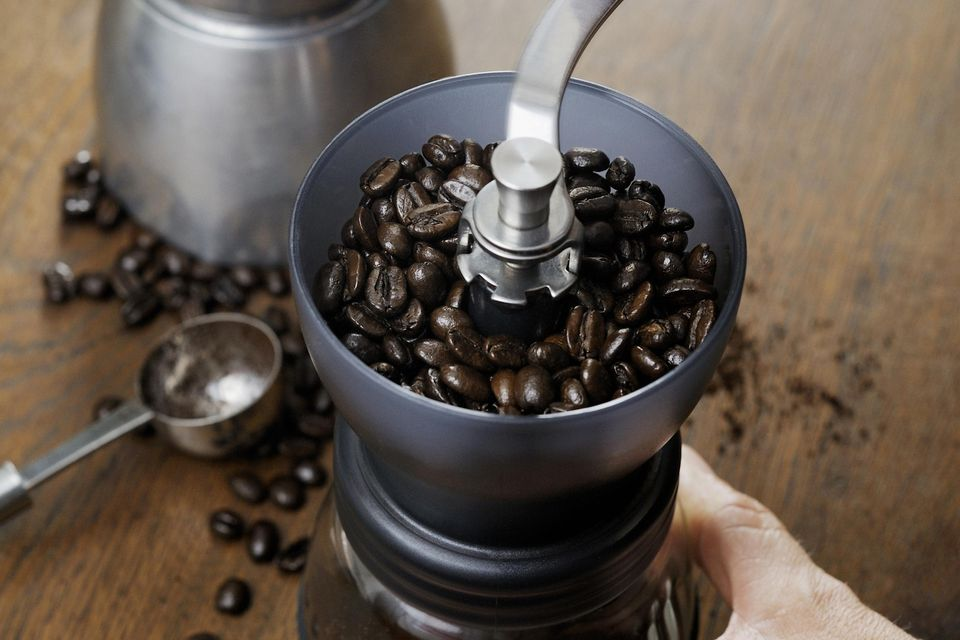 Coffee being ground in small handheld grinder.