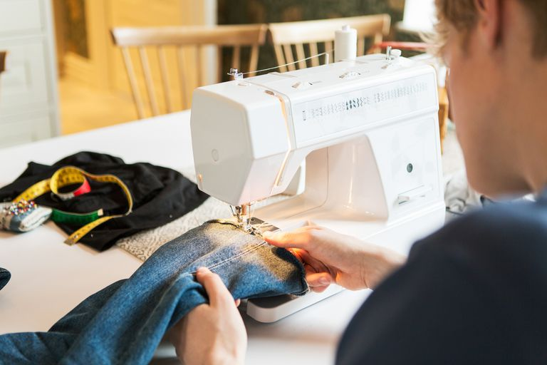 Cropped image of young man sewing denim jeans at home