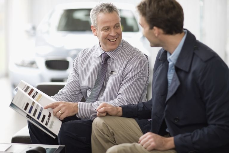 Car salesman talking with customer