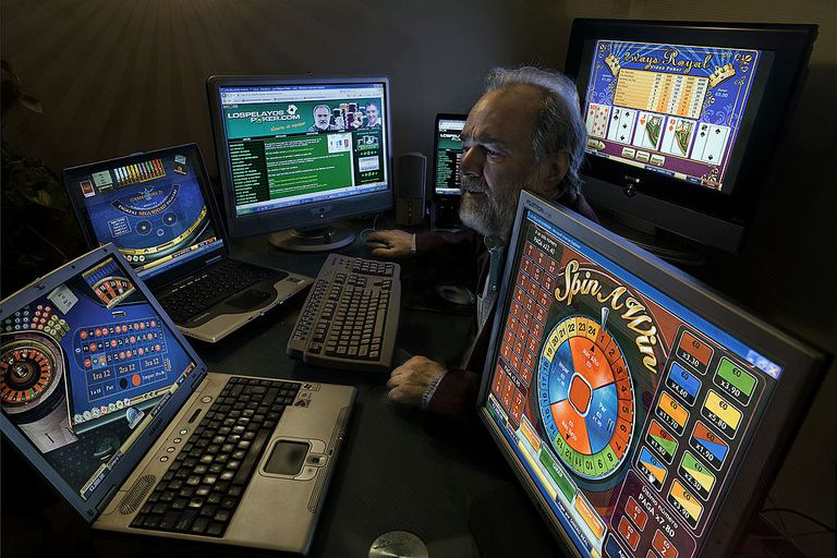 man surrounded by 6 different screens of online poker