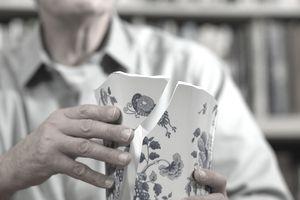 Mature man sitting at table repairing broken china vase
