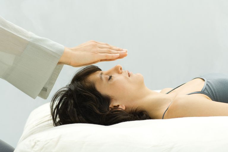 Woman undergoing alternative therapy treatment, therapist's hands over woman's head