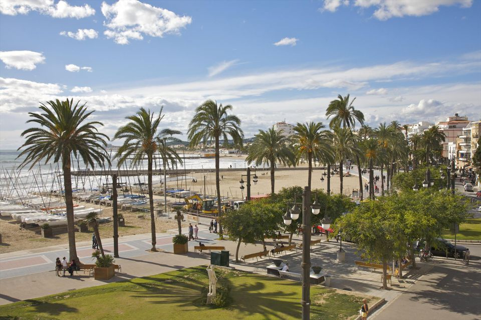 Palm trees, beaches, boats and Mediterranean Sea on an August afternoon from Placa del Baluard, Sitges, Catalonia (Catalunya) Spain.
