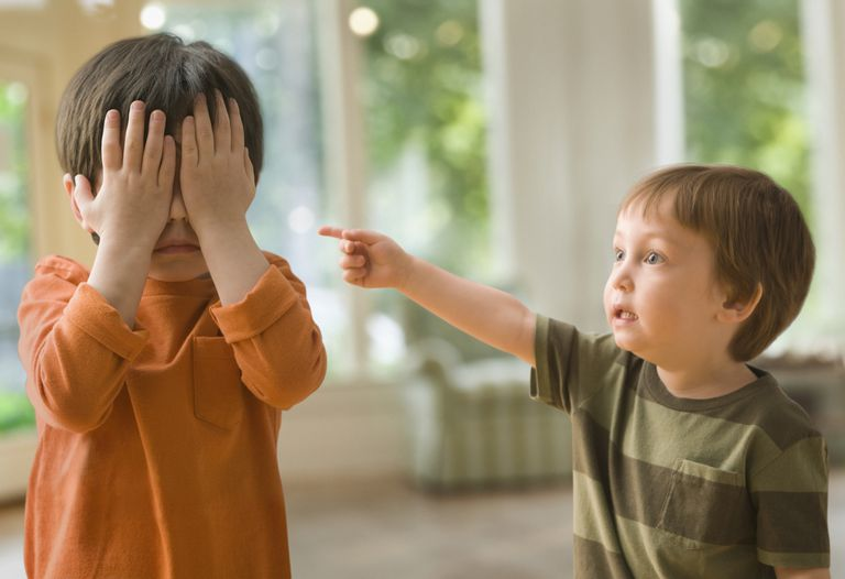 Mixed race boy pointing at brother who's covering his eyes