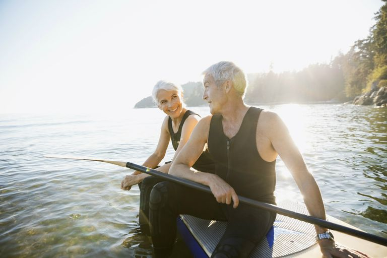 Senior couple on paddle board in ocean