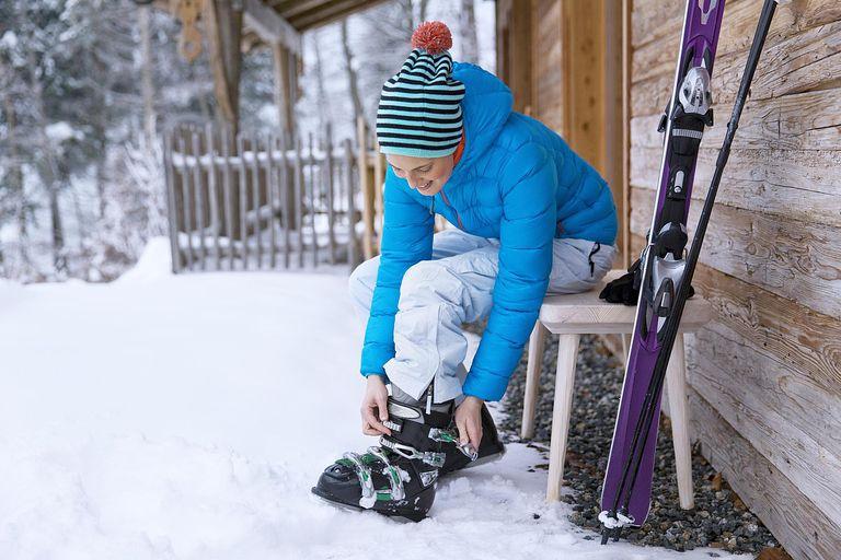woman adjusting ski boots in snow