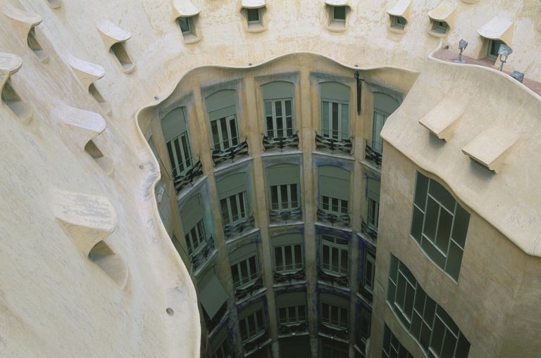 photo detail of building exterior, seen from a curved roof with dormers, looking at a wall of windows within a building wall well