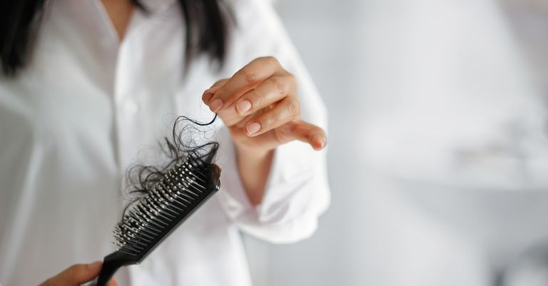 woman pulling hair out of brush