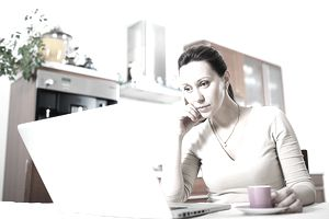 Mature Woman with Laptop and Coffee in the kitchen