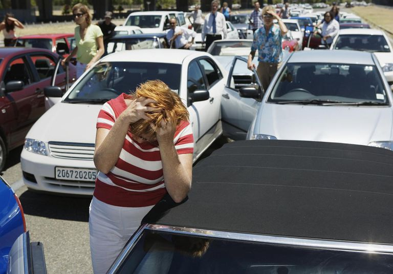Mature woman with hands in hair, standing by car in traffic jam