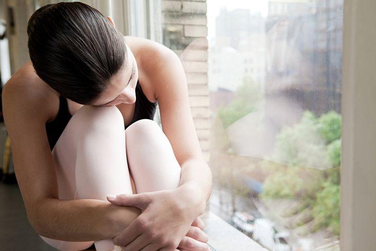 Ballerina by window, hugging her knees