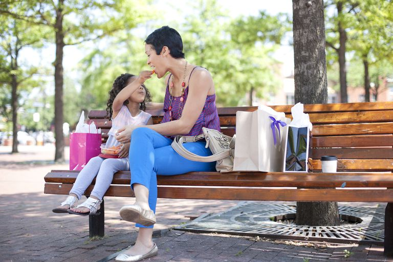 Mother and daughter eating on a park bench