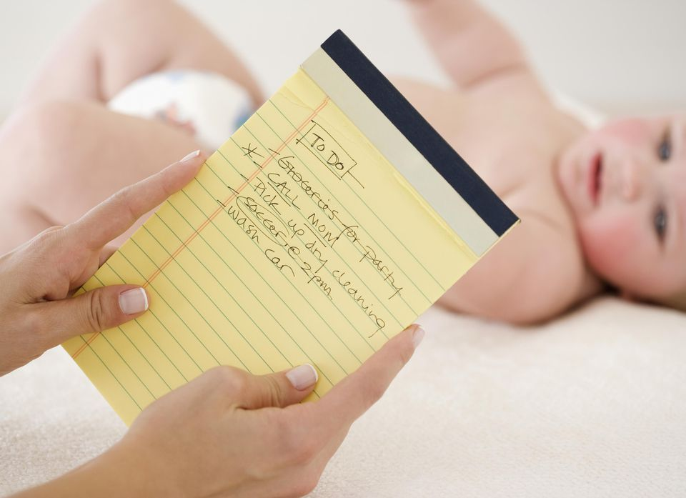 Mother looking at To Do list in front of baby