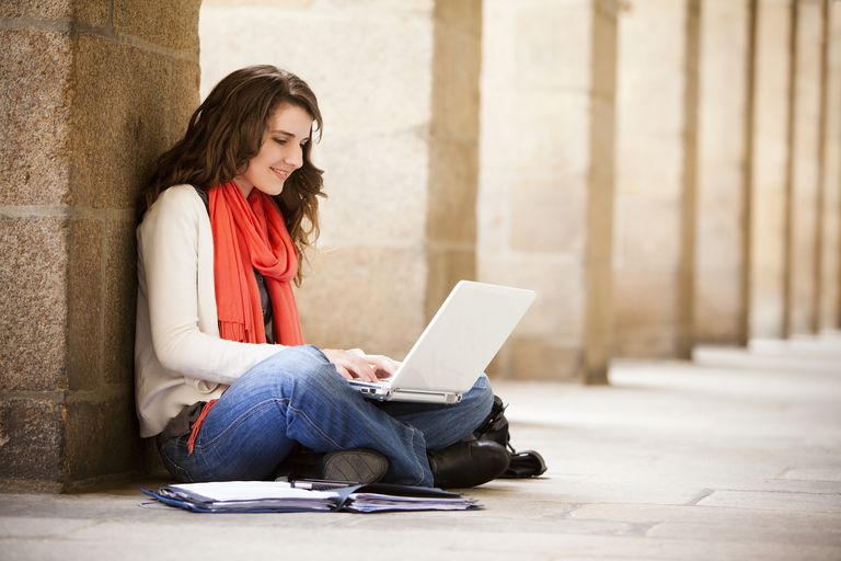 A woman sitting on the group with a laptop.