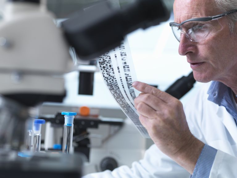 A medical researcher in a laboratory examining a DNA gel