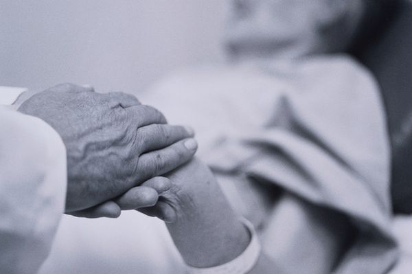 Doctor Holds Old Woman's Hand