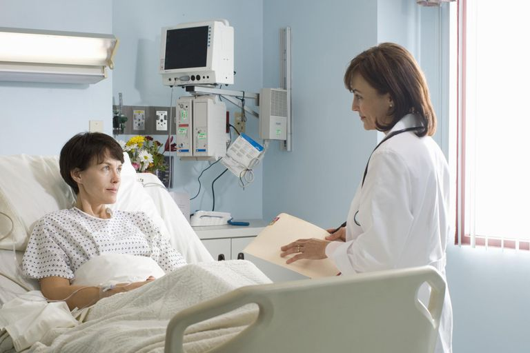 Female doctor talking to female patient lying in hospital bed
