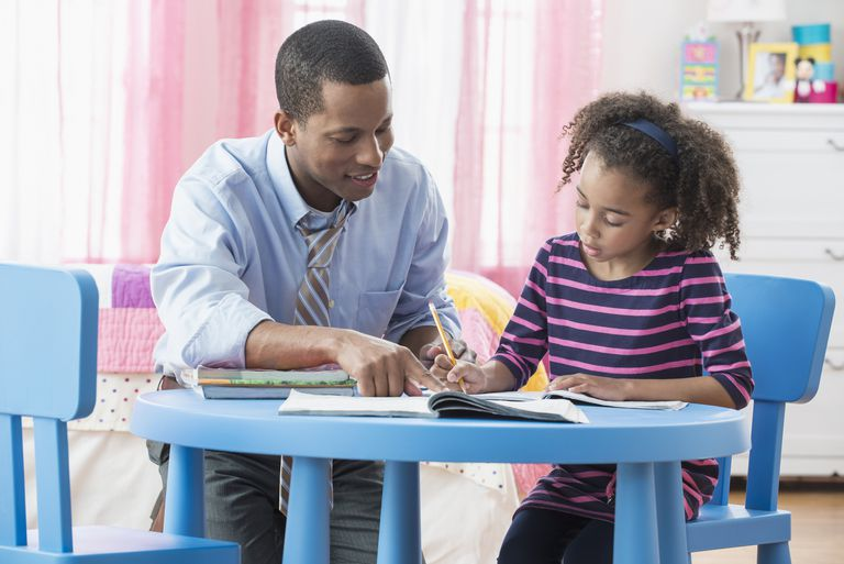 Father helping daughter with homework in playroom