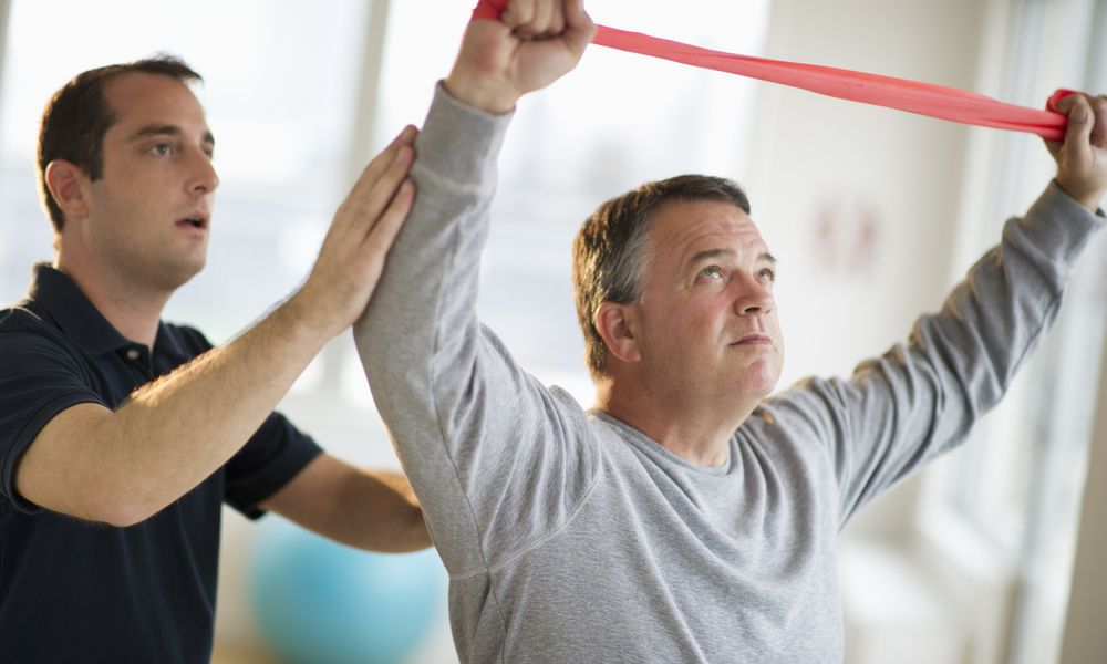 Physical therapist working with man exercising