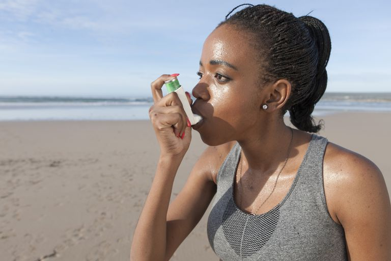 Woman using asthma inhaler on the beach