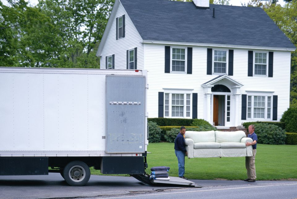 MOVING MEN UNLOAD FURNITURE FROM TRUCK