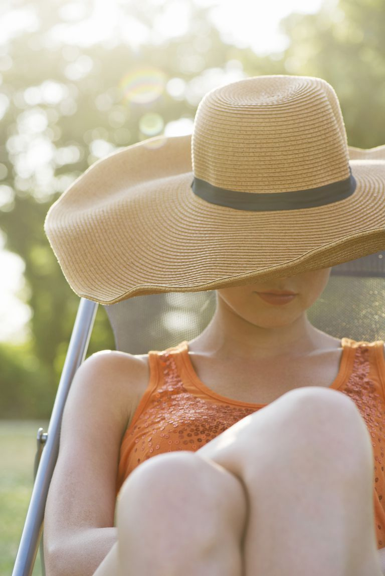 Young woman sunbathing outdoors, face covered