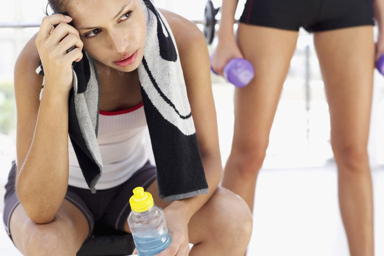 Young woman sitting in the gym with a bottle of juice and other person behind her