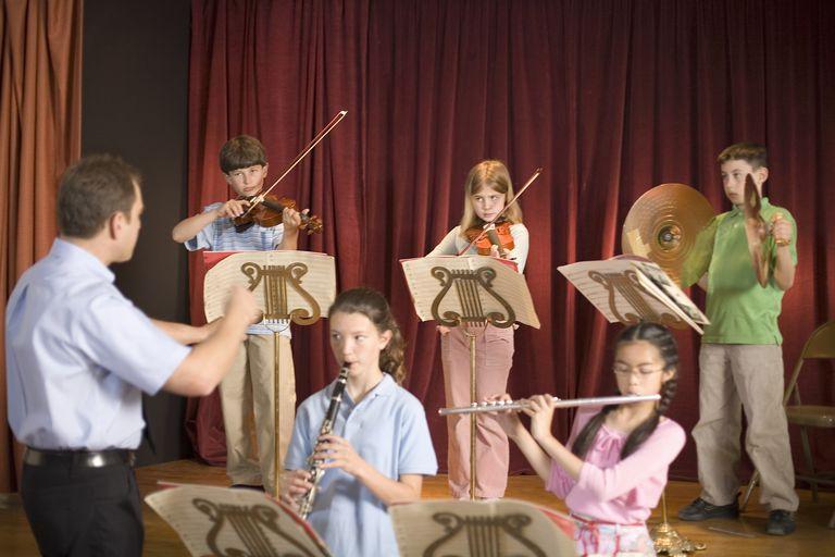 Music teacher instructing school orchestra
