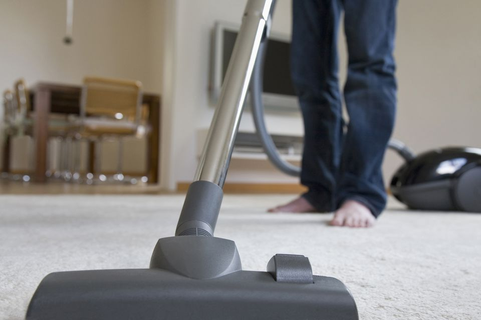 Germany, Baden-Wurttemberg, Stuttgart, Man vacuuming carpet, low section