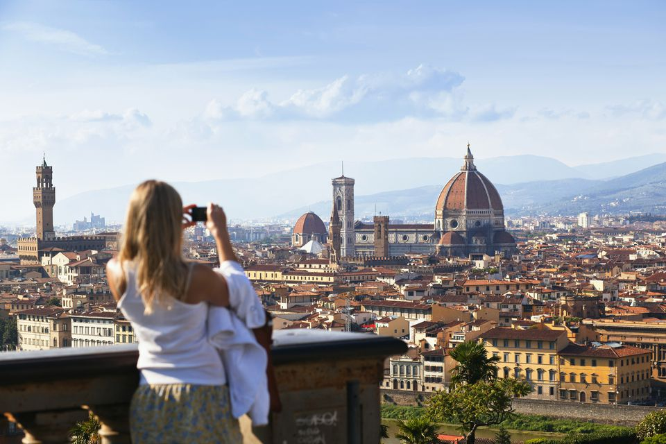 'Young woman taking a photo of the Florence skyline, view from Piazzale Michelangelo, Tuscany, Italy, Europe'