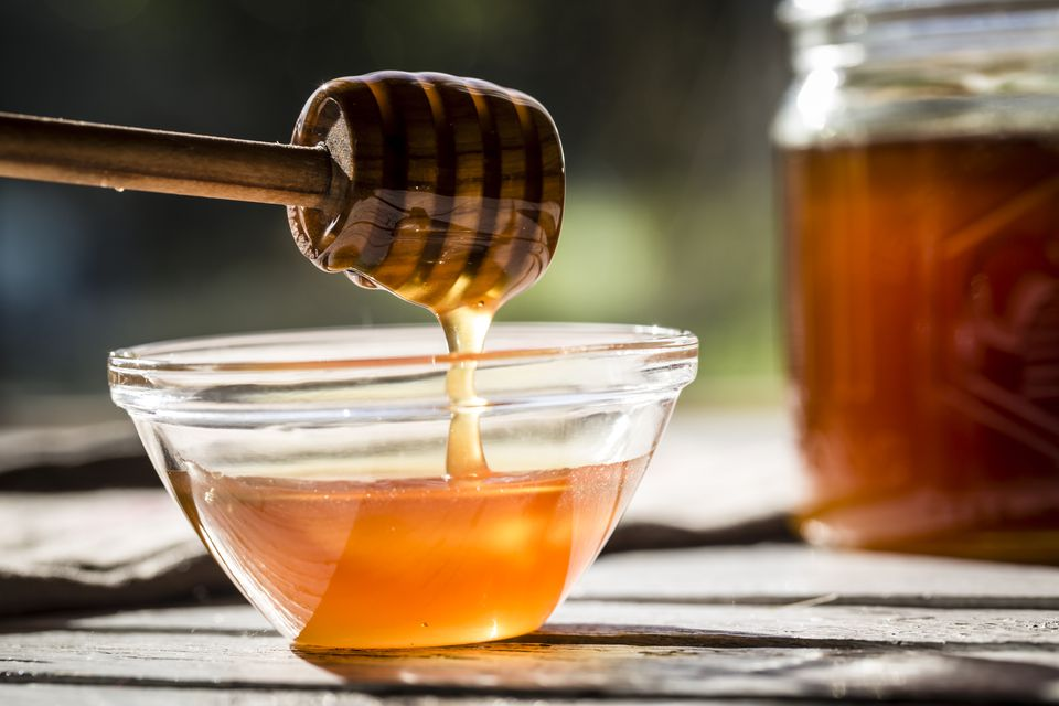 Honey dripping off a honey spoon into a glass bowl