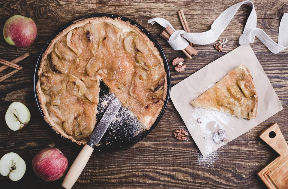 Homemade apple tart on wooden table viewed from above
