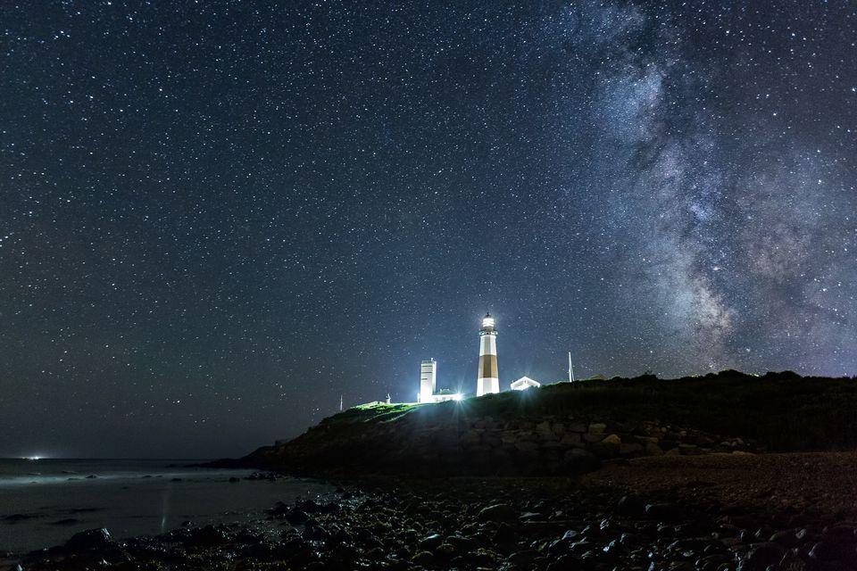 Montauk Point Long Island at night. Beach, lighthouse, Milky Way galaxy.