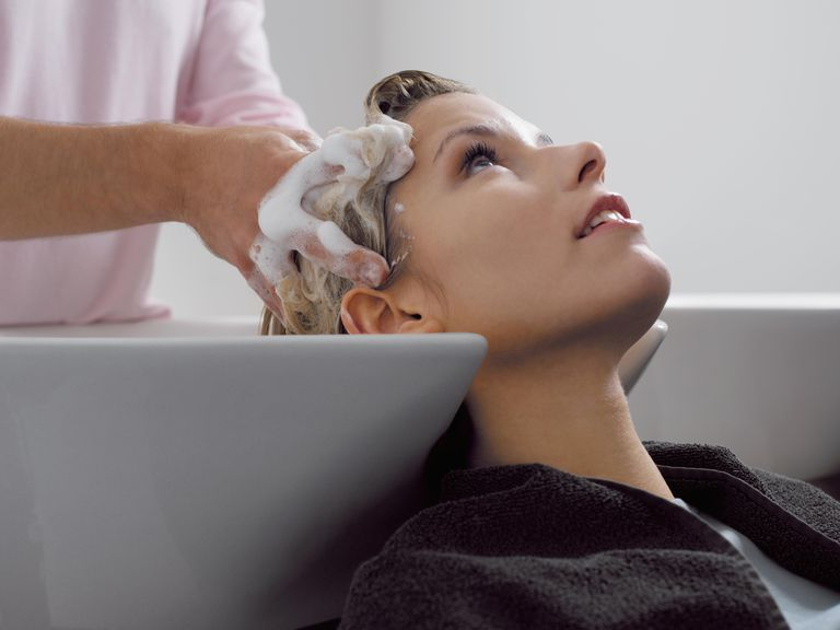 Woman Sitting at a Sink Having His Hair Washed by a Hairdresser