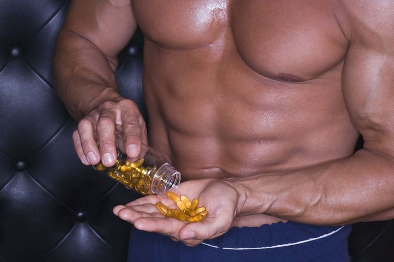 A bodybuilder with a handful of pills.