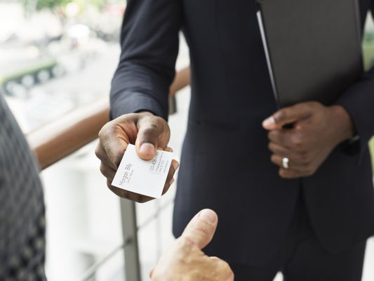 Businessman holding business card giving to another