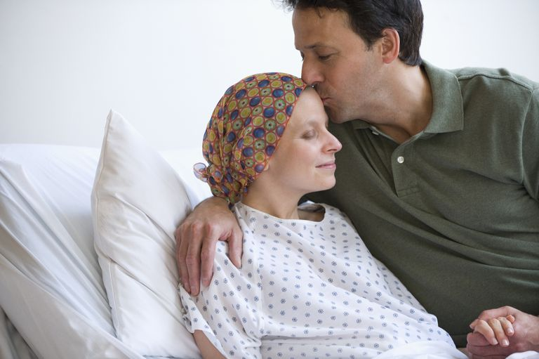 Husband at sick wife's side in the hospital