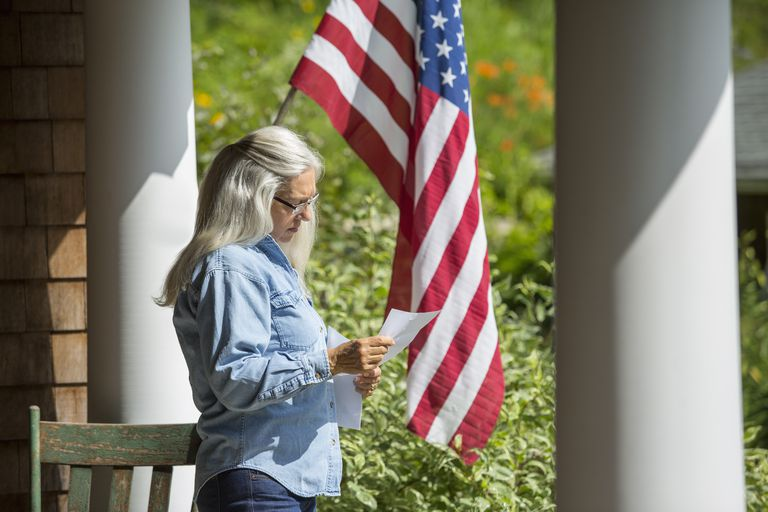 Woman with American flag and a letter.