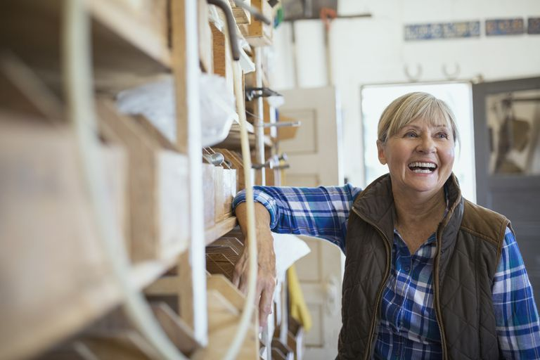 Laughing woman leaning on shelf in workshop