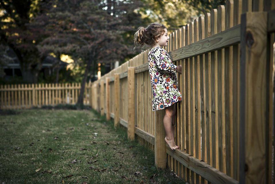 girl (4 yrs) peeking over fence