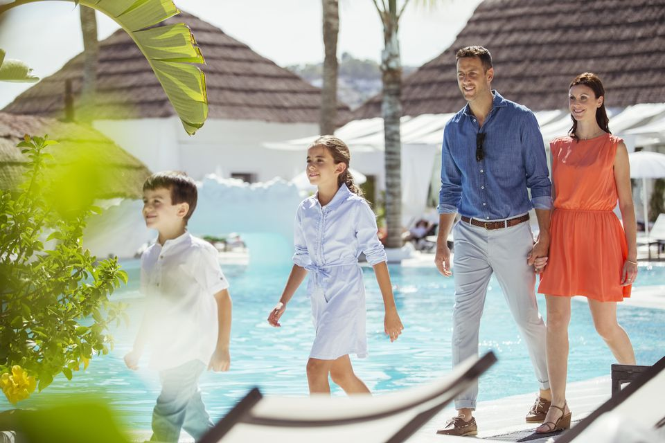 Family with two children walking together by swimming pool