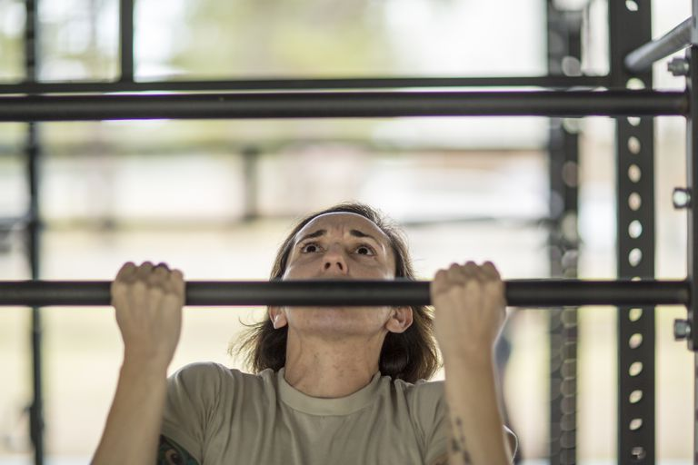 Female soldier doing pull ups at military air force base