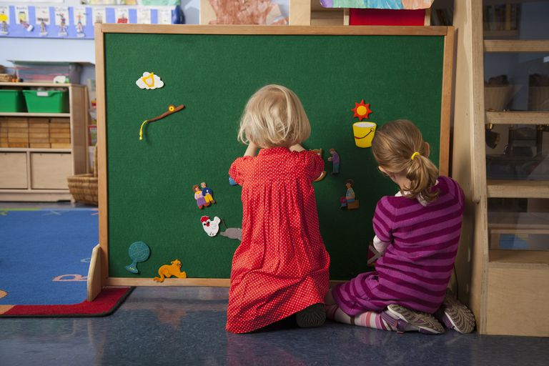 Two girls playing on a green felt board