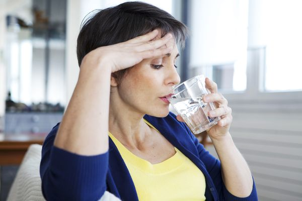 Woman drinking glass of water during hot flash